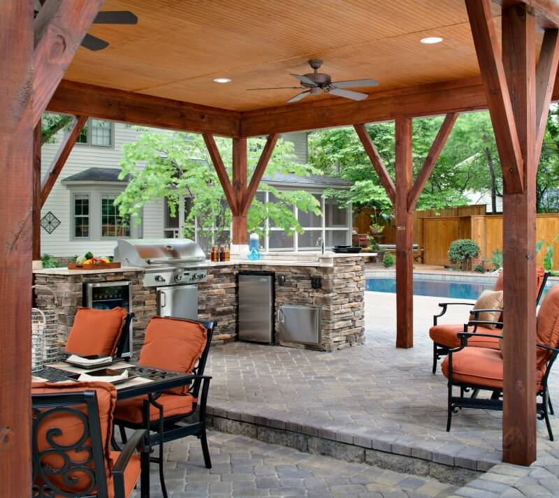 Detached-poolside-covered-paver-patio-with-integrated-outdoor-fireplace
