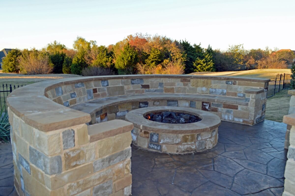 Custom stone fire pit with seating wall
