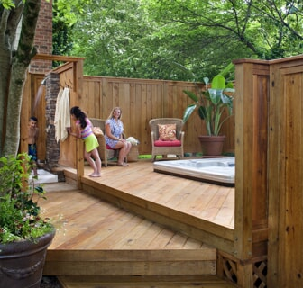 family enjoying deck with in ground hot tub and outdoor shower