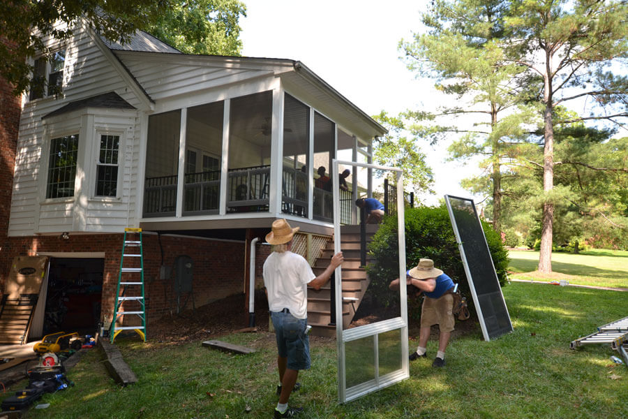 Family working on window to a screened porch