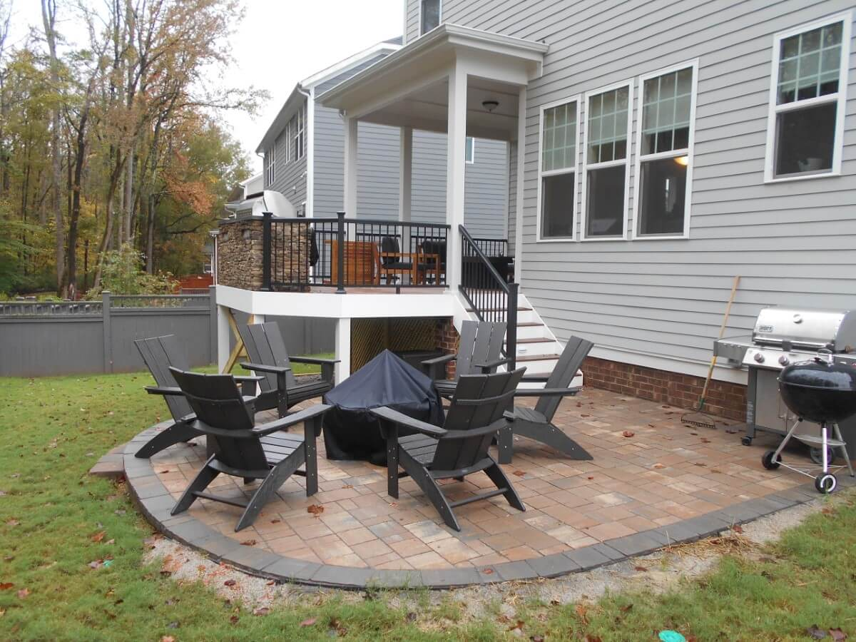 Raleigh backyard with paver patio and fire pit a deck and a covered porch