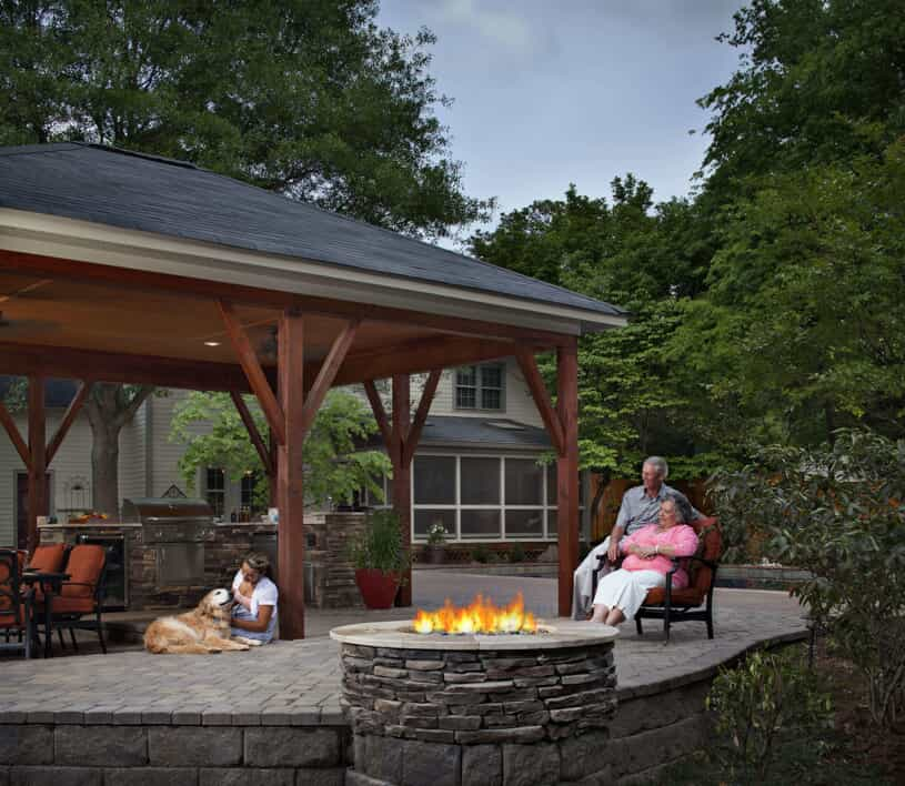 Family with a dog sitting on patio with a covering and a firepit
