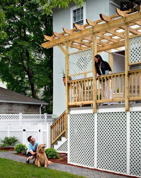 Woman speaking to man and dog below from raised deck with pergola