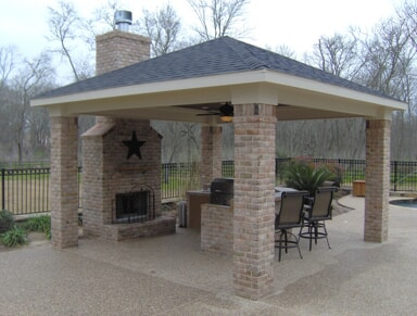 covered patio with brick pillars and fireplace