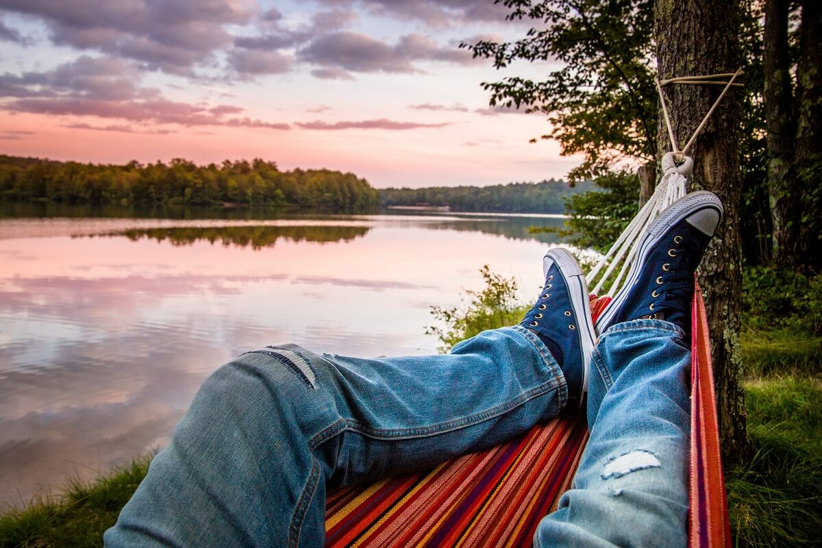person's legs in hammock with lake view
