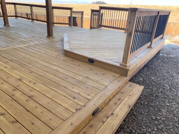 multi level wood deck with railings and pillars