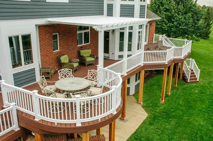 Second story wooden deck with white railing and outdoor furniture