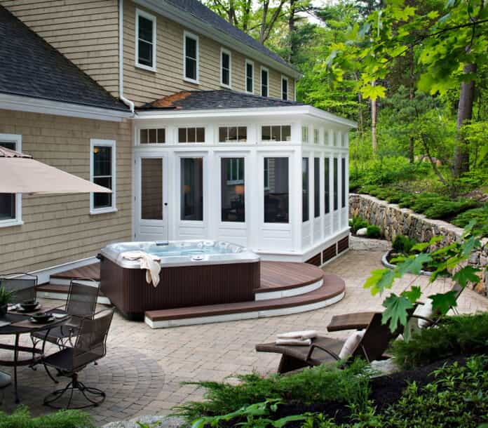 white screened porch with a Jacuzzi next to it on a patio outside