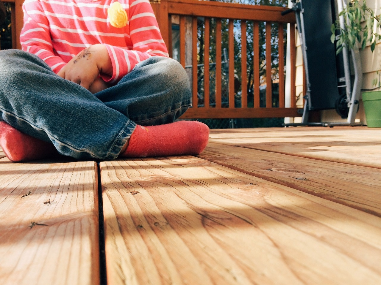 Child wearing jeans and red socks sitting on wooden deck
