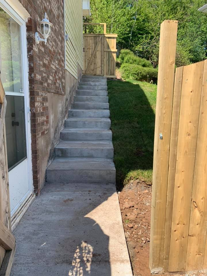 concrete stairs alongside a home with wooden fences