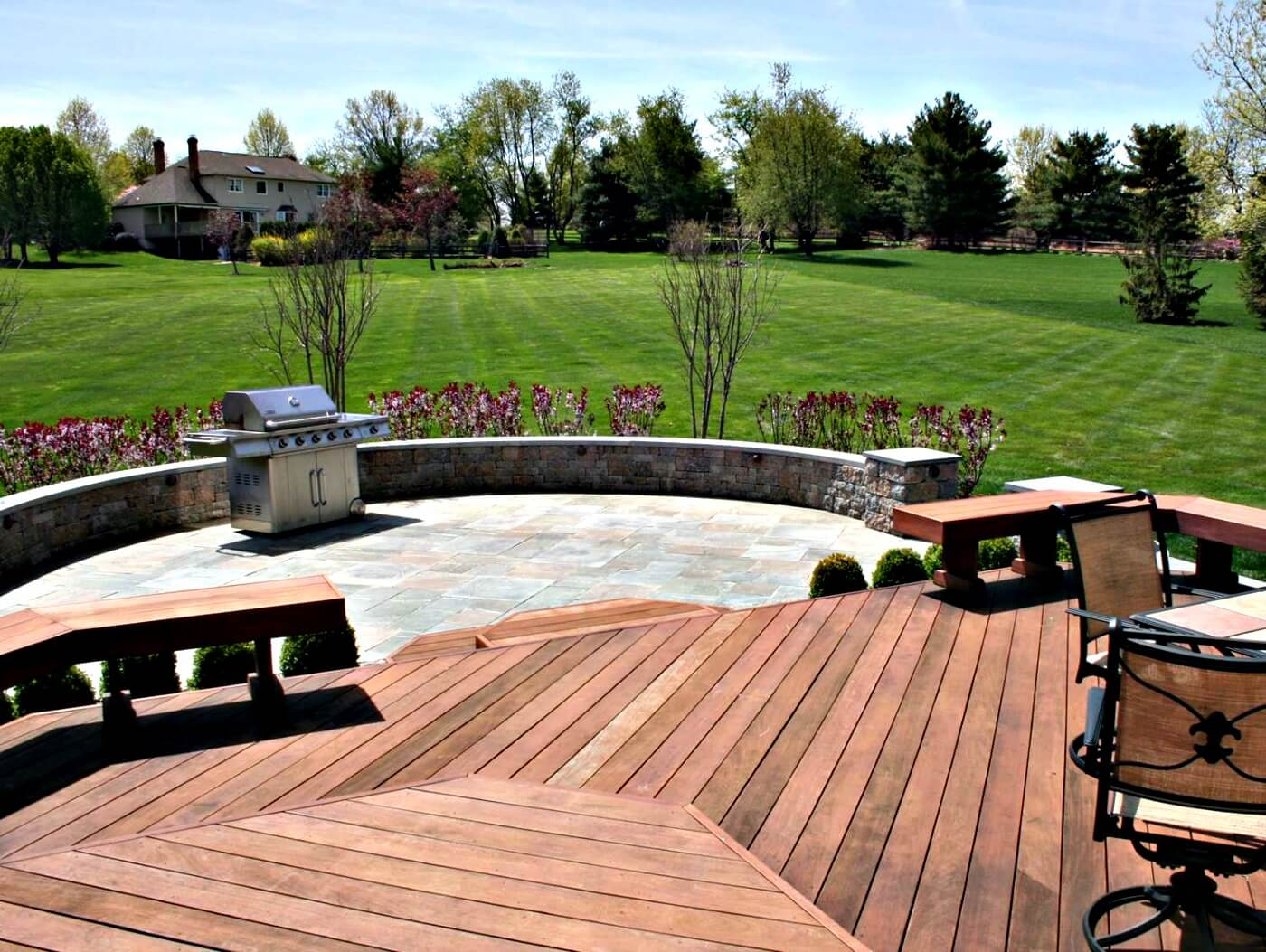 Custom backyard patio and wood deck with outdoor kitchen