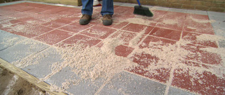 polymeric sand being swept into pavers